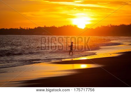 Happy young fisherman boy at sunset on the beach pulling fish. Bali Indonesia