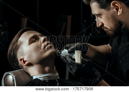 BARBERSHOP THEME. BEARDED BARBER IN BLACK RUBBER GLOVES IS TRIMMING THE BEARD OF HIS YOUNG HANDSOME CLIENT WITH CLOSED EYES. HE IS USING A CUTTING COMB AND A HAIR CLIPPER