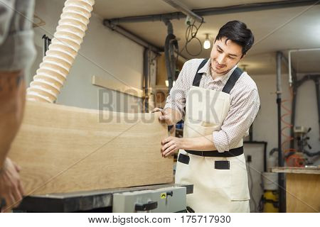 Worker processes board on woodworking machine. Young man dressed in protective overalls, checkered shirt and jeans. Room equipped with hood.