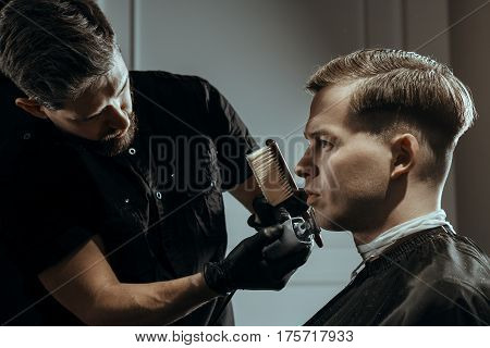 BARBERSHOP THEME. BEARDED BARBER IN BLACK RUBBER GLOVES IS TRIMMING THE BEARD OF HIS YOUNG SERIOUS CLIENT. HE IS USING A CUTTING COMB AND A HAIR CLIPPER