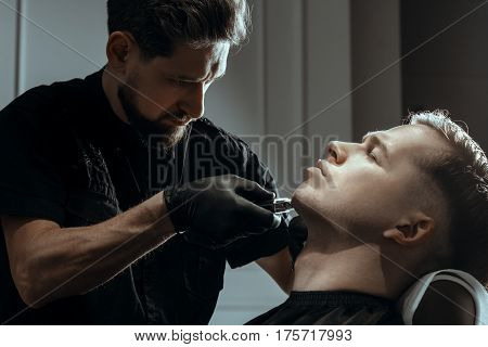BARBERSHOP THEME. BEARDED FOCUSING BARBER IN BLACK RUBBER GLOVES IS TRIMMING THE BEARD OF HIS YOUNG HANDSOME CLIENT WITH CLOSED EYES. HE IS USING A HAIR CLIPPER