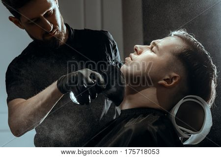 BARBERSHOP THEME. BEARDED BARBER IN BLACK RUBBER GLOVES APPLIES TALC BY BRUSH ON CLIENT'S SKIN