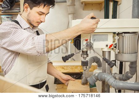 Brunette man bored wooden board on drilling machine. Woodworking drill installed on machine with engine. Mounted hoods to place of drilling.