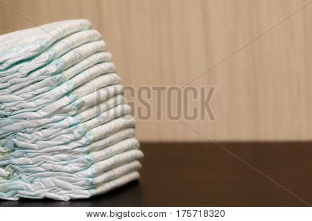 Stack of diapers or nappies on table with copyspace closeup
