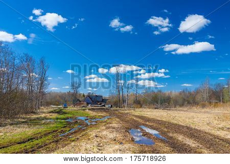 Road with big puddle on the field on countryside toward to wooden house and blue sky reflection in puddles on sunny spring day