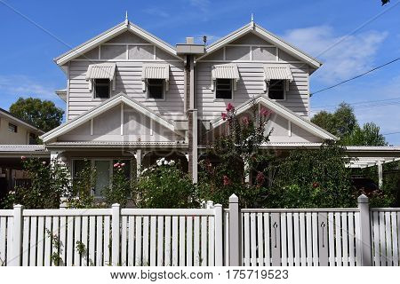 two cream weatherboard houses with white picket fence against blue sky