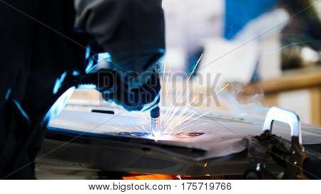 Welding industrial: worker in helmet repair detail in car service, telephoto