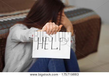 Woman holding sheet of paper with word HELP