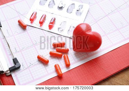 Pills and red heart on paper electrocardiogram