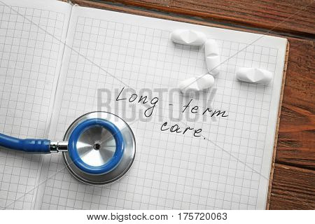 Stethoscope and notebook with text LONG-TERM CARE on wooden background
