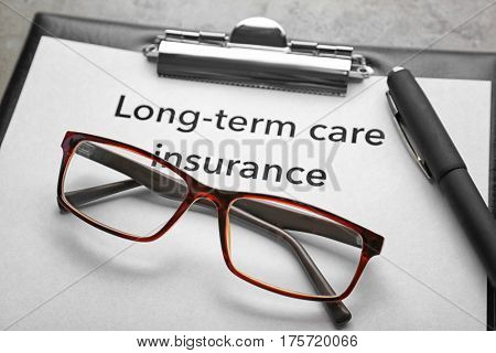 Text LONG-TERM CARE INSURANCE on clipboard with pen and glasses closeup