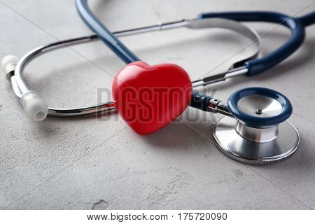 Stethoscope and red heart on light background