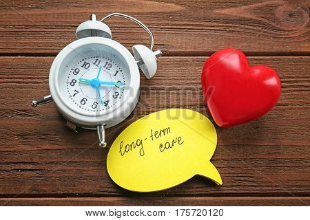 Red heart, alarm clock and sticker with text LONG-TERM CARE on wooden background