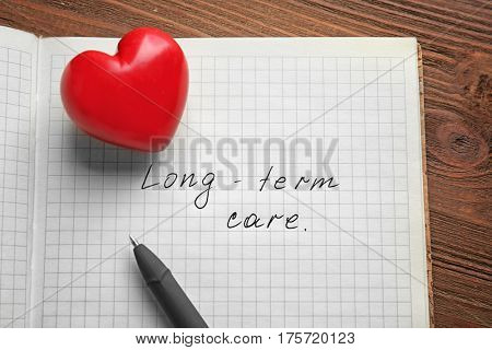Red heart and notebook with text LONG-TERM CARE on wooden background