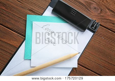 Paper note with text LONG-TERM CARE and pencil on wooden background