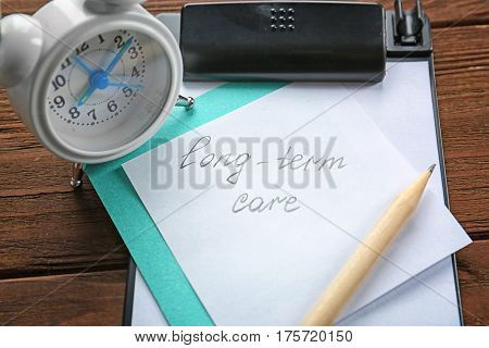 Paper note with text LONG-TERM CARE and alarm clock, closeup