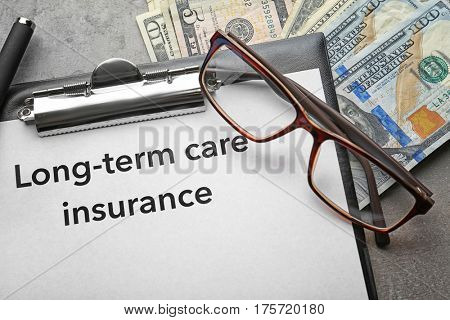 Text LONG-TERM CARE INSURANCE on clipboard with glasses and dollars closeup