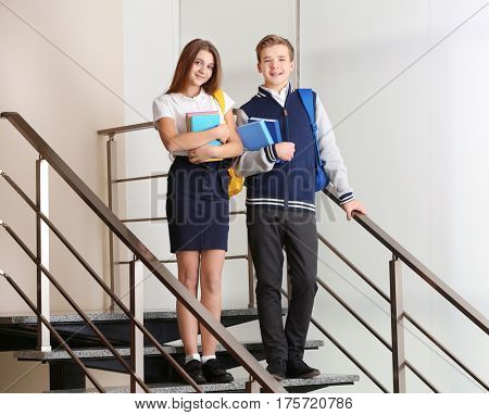Teenagers with backpacks and books standing on stairs