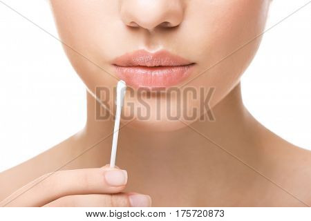 Woman touching lips with cotton swab on white background