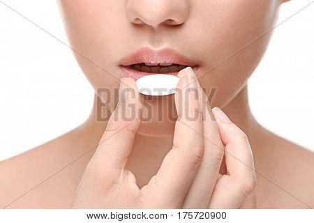 Woman taking pill on white background, closeup