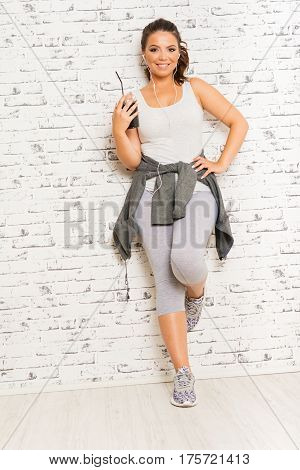 Beautiful young fitness woman with cup of coffee, smiling, standing against brick wall. Fit girl in gray sportswear posing.