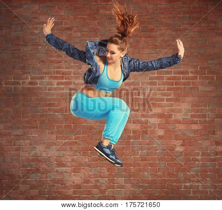 Beautiful young hip-hop dancer jumping against brick wall