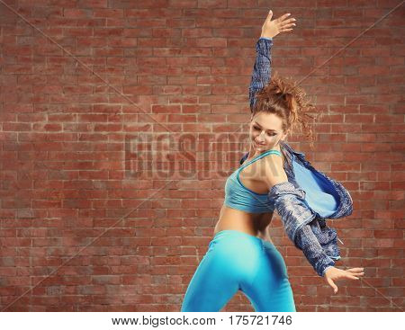 Beautiful young hip-hop dancer near brick wall