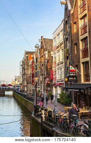 Amsterdam, Netherlands - April 1, 2016: Traditional old buildings, people, canal and bridge view with bicycles in Amsterdam, Holland