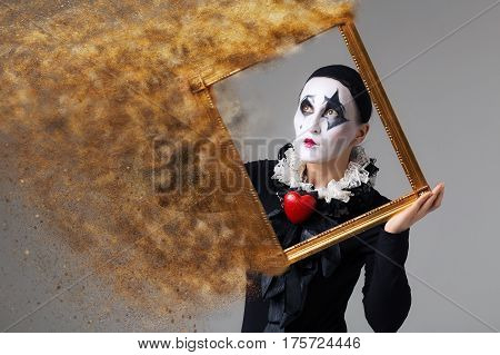 Woman in disguise harlequin in the picture frame.