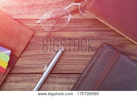 Several vintage Leather Items on dark natural Wood Background with clear wooden Texture in old style tones