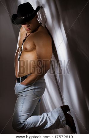 Muscular shirtless cowboy leaning against a white wall