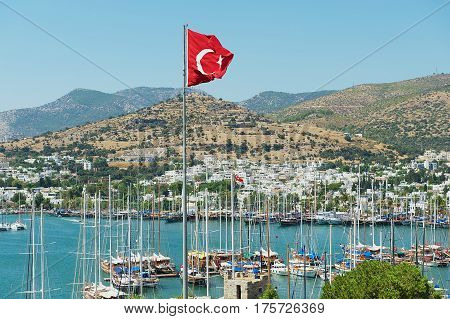 BODRUM, TURKEY - AUGUST 15, 2009: View to the marina with the Turkish National flag at the flagpole waving over a hill in Bodrum, Turkey.