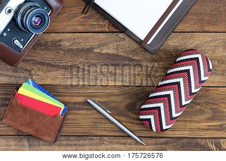 Top View of vintage Lifestyle Items Film Photo Camera Pen leather Notepad Credit Cards Glass Box on Wood Ba
