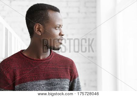 Profile Of Handsome African Young Student Wearing Casual Sweater Looking Through Window With Inspire