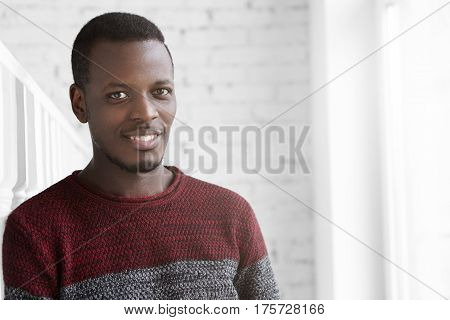 Handsome Confident Young African American Man Dressed In Casual Warm Sweater, Looking At Camera With