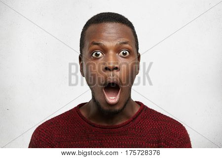 Portrait Of Fearful Bug-eyed Young African American Man In Casual Sweater Screaming In Shock, Keepin