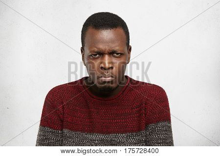 Headshot Of Grumpy Unhappy Young Dark-skinned Male Dressed Casually Frowning And Looking At Camera W