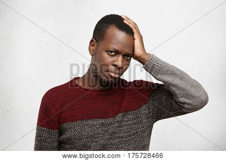 Portrait Of Handsome African American Young Male Dressed In Warm Casual Sweater Holding Hand On His