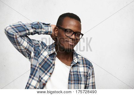 Studio Shot Of Handsome African American Hipster Wearing Trendy Glasses And Checkered Shirt Over Whi