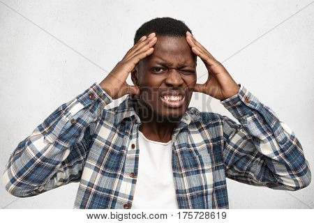 Indoor Shot Of Frustrated Annoyed Dark-skinned Student Having Bad Headache, Squeezing His Temples, L