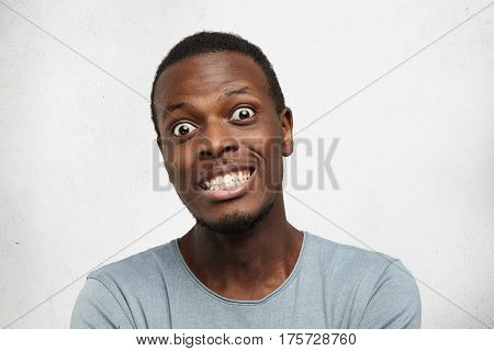 Portrait Of Funny Terrified Young African Man Bugging Eyes Out, Showing Teeth, Looking At Camera Wit
