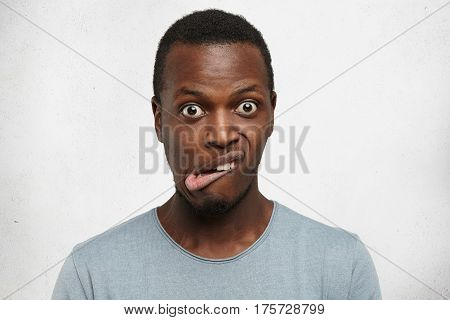 Indoor Shot Of Emotional Young Dark-skinned Man In Grey T-shirt Grimacing, Bugging Eyes Out, Making