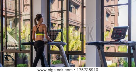 Horizontal shot of woman jogging on treadmill at health sport club at luxury resort. Female working out at a gym running on a treadmill with a great summer view at spa facility at hotel during summer vacation.