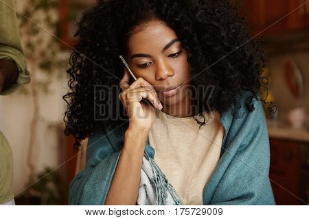 Serious Young Dark-skinned Female With Afro Hairstyle Having Worried And Unhappy Look While Talking