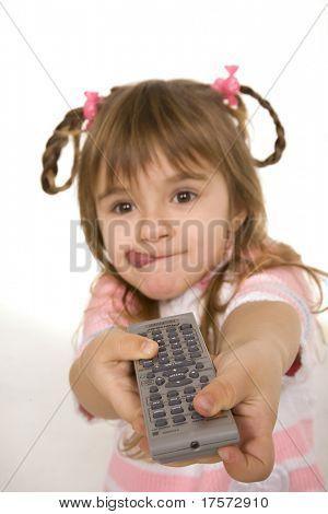 Joyful little girl holding tv remote control