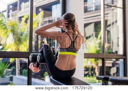 Attractive fit woman working out abs in fitness gym at luxury resort hotel with a great view during summer vacation.