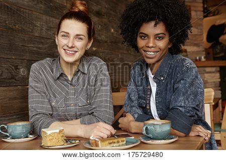 Indoor Shot Of Happy Cheerful Samesex Interracial Female Couple Having Coffee And Dessert At Restaur