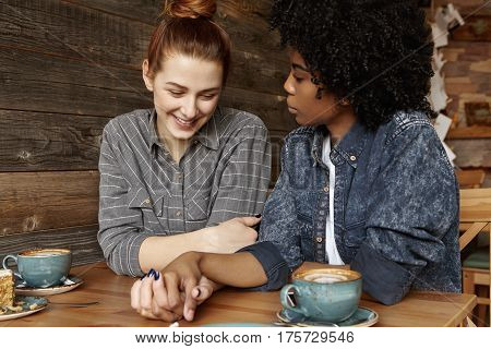 Shy Beautiful Redhead Woman With Hair Bun Smiling Joyfully Sitting At Coffee Shop With Fashionable A