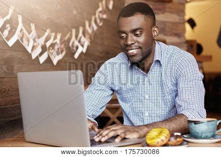Happy Handsome Young Dark-skinned Businessman Relaxing At Cafe During Breakfast, Typing On Generic L