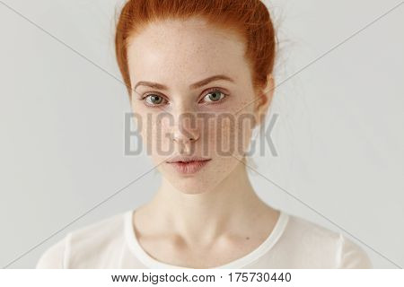 Close Up Studio Shot Of Beautiful Charming Redhead European Model With Healthy Freckled Skin Looking